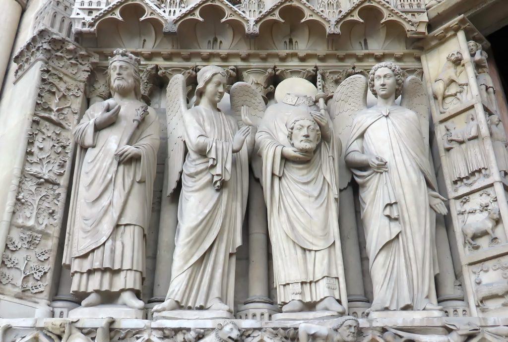 Statue de Saint-Denis portant sa tête dans ses mains, portail gauche de la cathédrale Notre-Dame à Paris. Photo : DEZALB - Pixabay